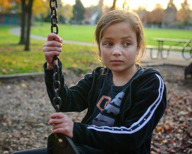 Worried girl on a swing,