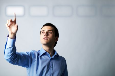 Young businessman pointing a virtual button.