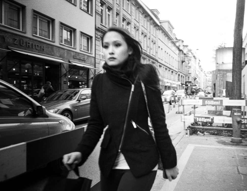 Picture of a woman looking shut off moving quickly through a city