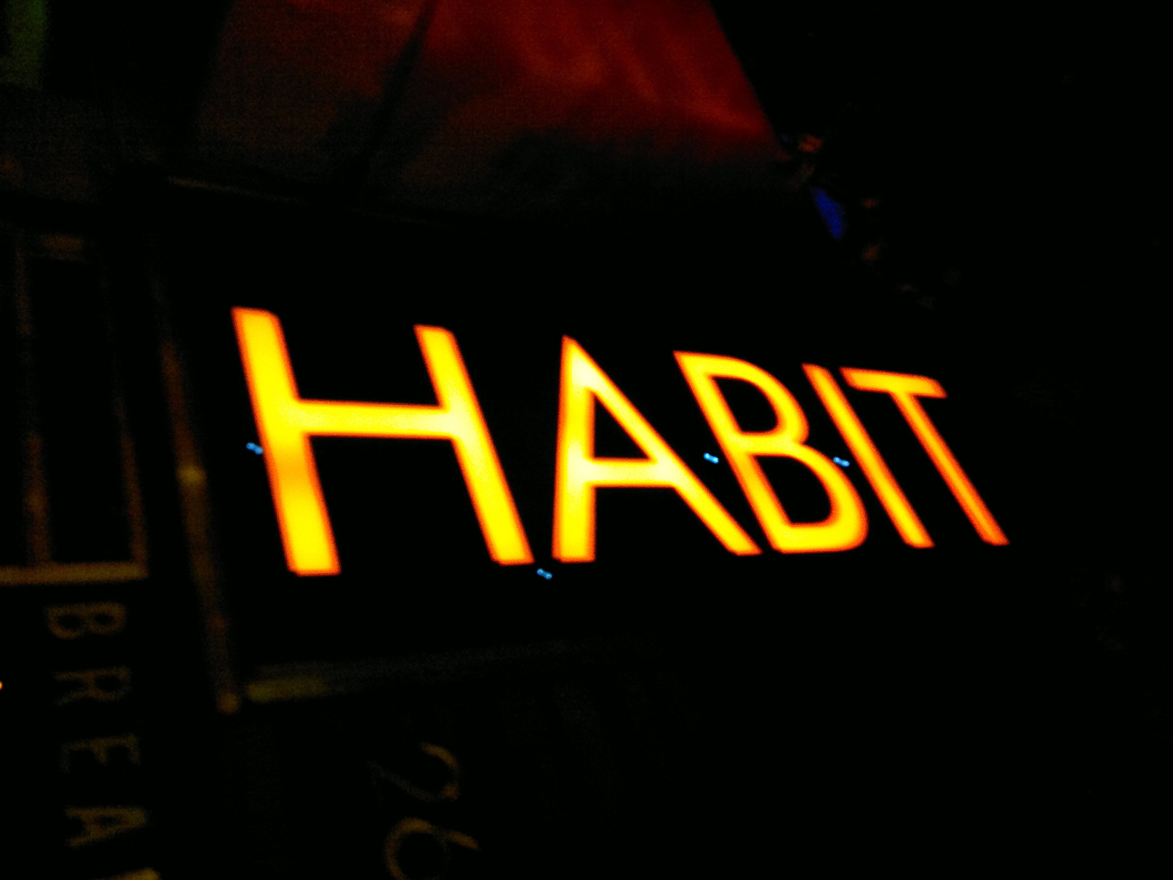 Picture of a neon sign that says Habit