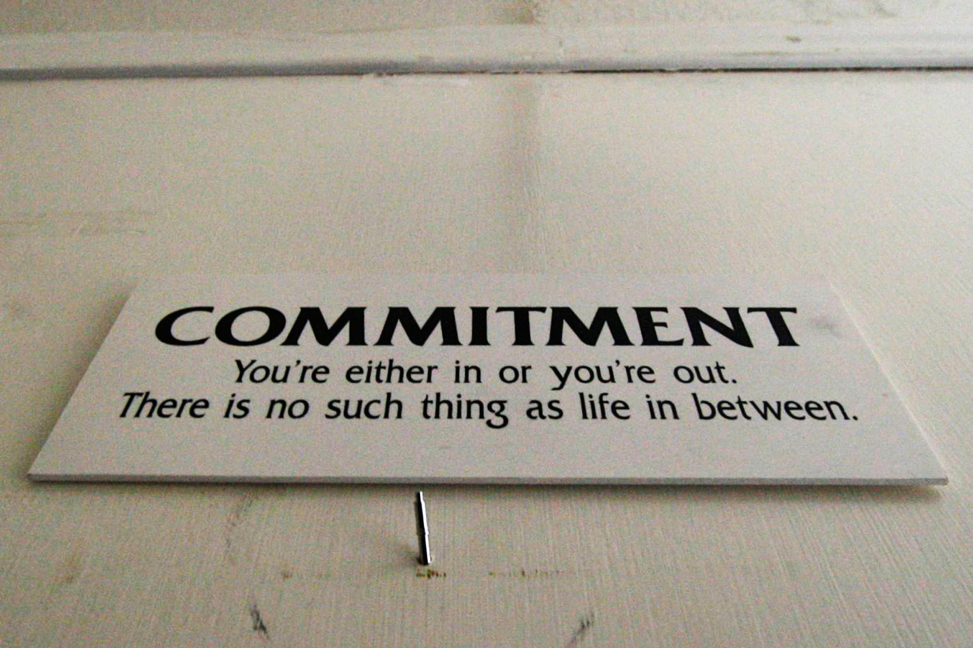 Picture of a sign on a wall that says 'Commitment'