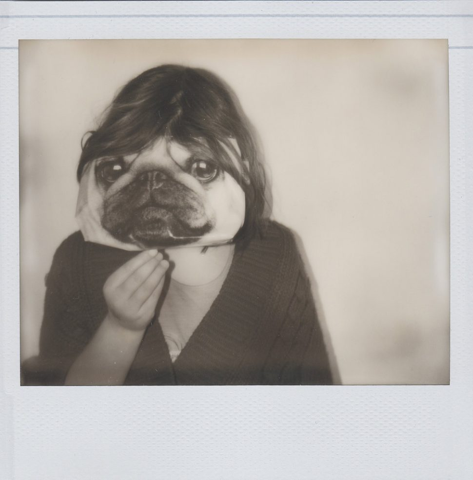 Picture of a woman holding a dogs face in front of her's