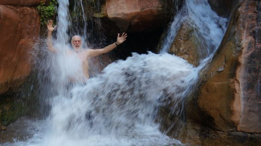 A Happy Man Dancing In A Waterfall